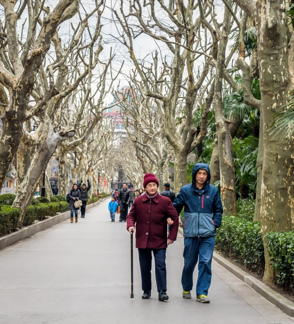 A man taking his mother for a walk in Fuxing Park in Shanghai