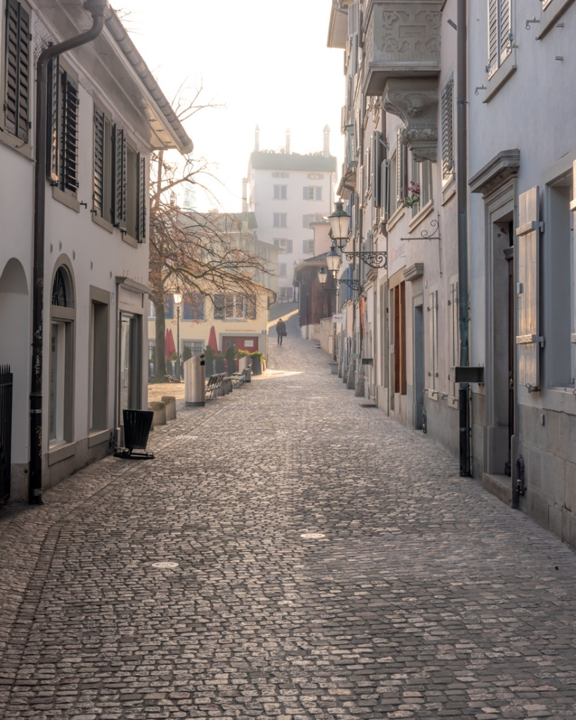 A cobbled alleyway in Zurich in soft sunlight