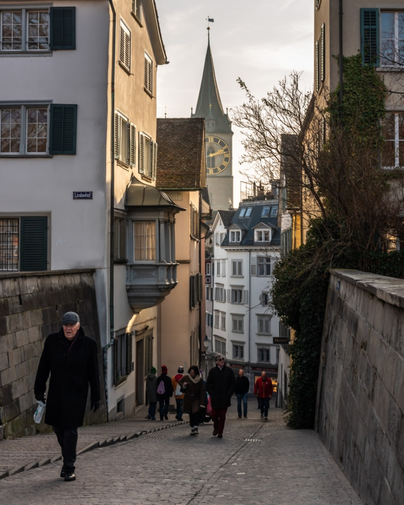 People walk up a cobbled lane in Zurich with a church spire in the background.