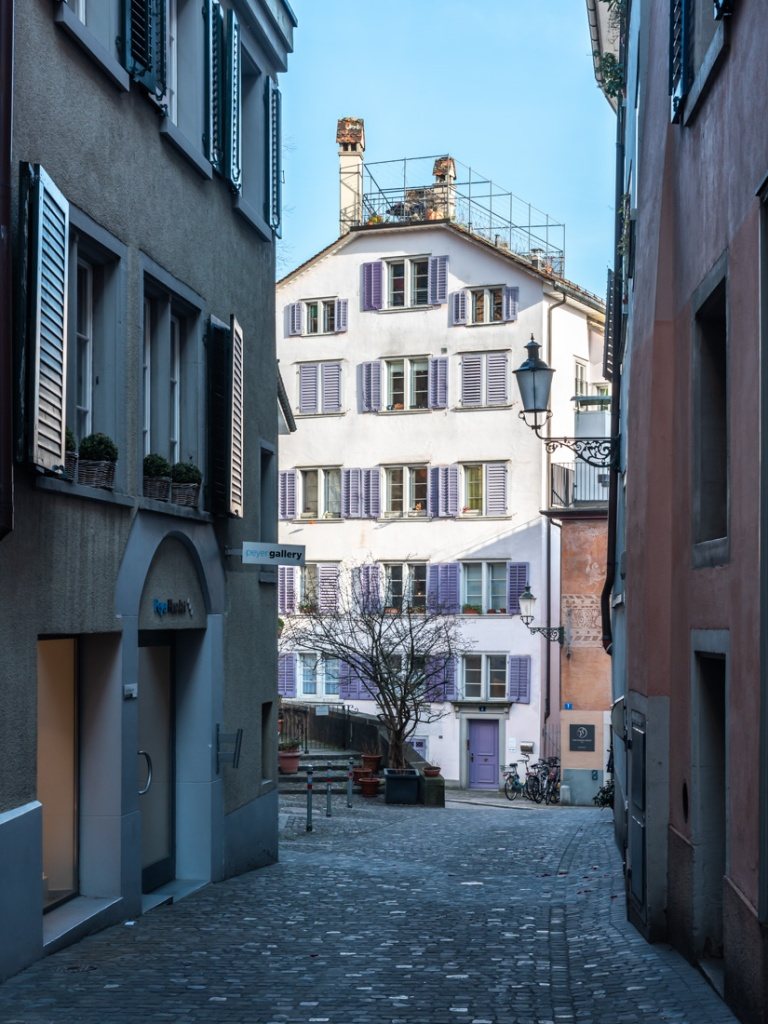A cobbled alleyway in Zurich with a historic building with magenta window shutters.